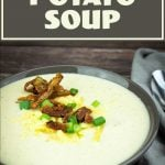 loaded potato soup in a bowl with cheese, green onions, crispy bacon, and crispy potato skins on top