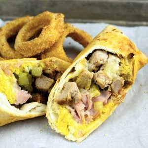 Air Fryer Cuban Wrap cut in half on parchment with onion rings behind it