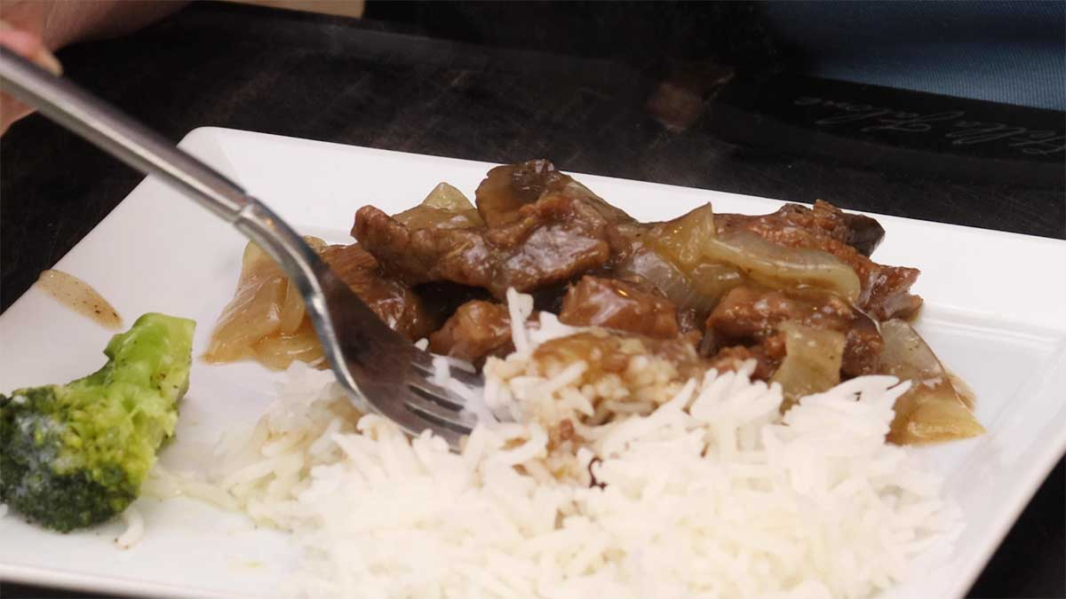 serving beef tips and rice with gravy and broccoli on a plate