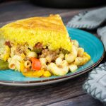 southwestern goulash with cornbread topping on a blue plate
