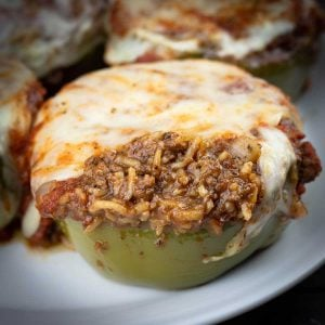 Stuffed peppers on a white plate with cheese melted on top