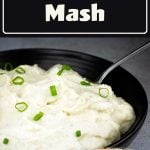 mashed cauliflower in a black bowl with green onions on top