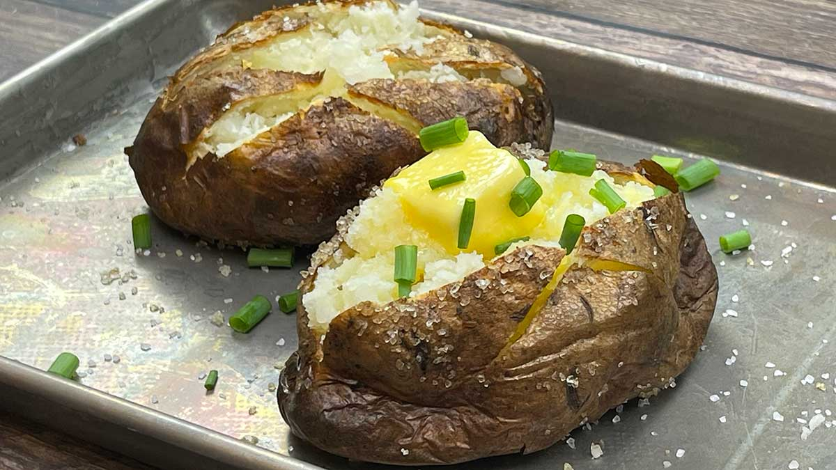 two baked potatoes on a tray one plain and one has butter and chives on it
