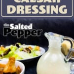 creamy caesar dressing in a glass container next to croutons and a caesar salad