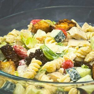 caesar pasta salad in a large glass bowl