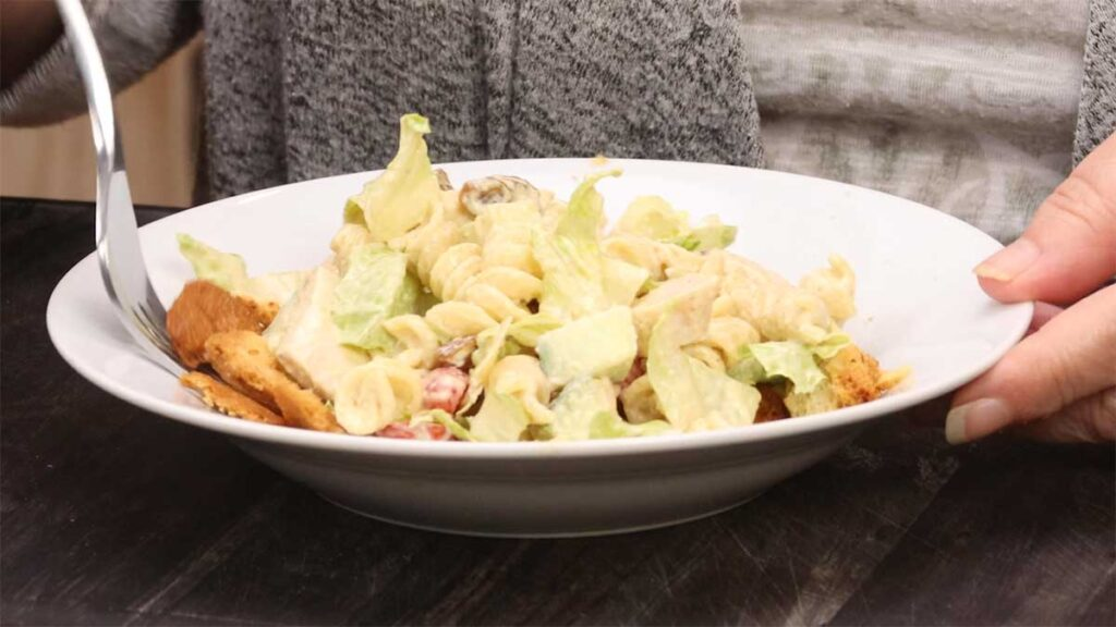 caesar pasta salad in a white bowl with a fork