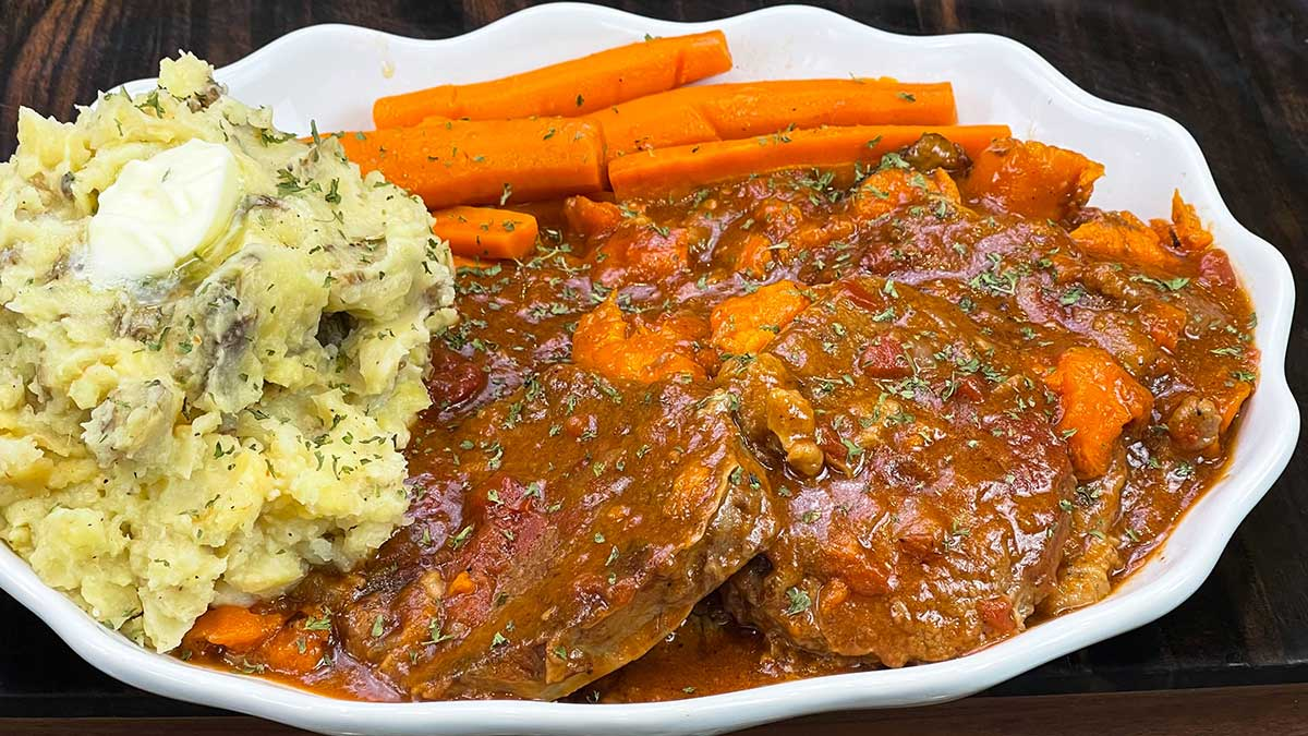 swiss steak on a platter with mashed potatoes and carrots